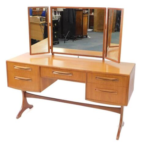 A G plan teak dressing table, with a tryptic mirror back, over a central fitted jewellery drawer, flanked by four further drawers, raised on X shaped end supports united by a single stretcher, 131.5cm high, 137cm wide, 46cm deep.