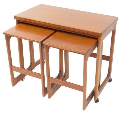 An A H Mackintosh & Company Ltd teak trolley, with a fold over top, enclosing two smaller tables, raised on curved supports, on casters, largest table 63cm high, 76cm wide, 40cm deep.