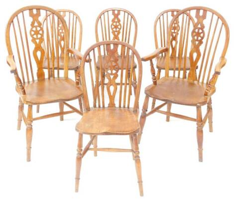 A set of six 19thC oak and elm wheelback dining chairs, with solid saddle seats, raised on turned legs united by an H frame stretcher, comprising pair of carvers and four single chairs.