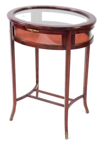 A French 19thC style mahogany bijouterie table, of oval form, with glazed hinged lid and sides, raised on tapering out swept legs united by a double H framed stretcher, 76cm high, 48.5cm wide, 48cm deep.