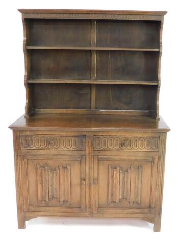 An oak dresser, the out swept pediment above a two shelf plate rack, over two frieze drawers above linenfold panelled doors, raised on channel square legs, 182.5cm high, 127 cm wide, 38cm deep.