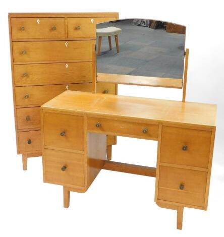 A mid century Georgian style light oak chest, of two short over five long drawers, raised on tapering square legs, 128cm high, 84cm wide, 45cm deep, together with a dressing table, the domed swing framed mirror over one long flanked by four deep drawers,