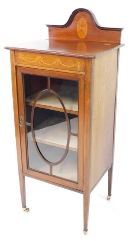 An Edwardian mahogany and inlaid display cabinet, the domed back with paterae inlay, over a glazed door enclosing two shelves, raised on tapering square legs, brass capped on castors, 122cm high, 50.5cm wide, 41cm deep.