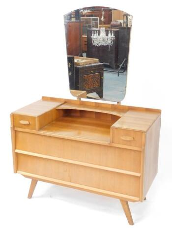 A 1950's vintage walnut dressing chest, possibly by Alfred Cox, the shield shaped mirror above a shallow curved shelf, flanked by two short drawers over two long drawers, raised on out swept legs, 144.5cm high, 99cm wide, 44cm deep.