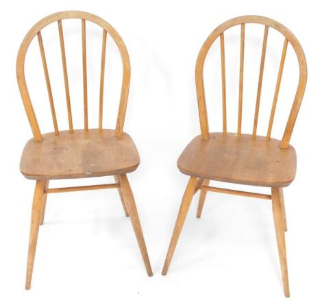 A pair of Ercol mid century ash and elm Windsor kitchen chairs, with solid seats, raised on turned legs united by an H frame stretcher.