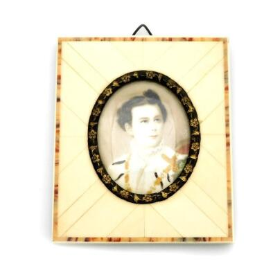 A late 19thC portrait miniature of a military gentleman, depicting a man in dress uniform possibly Ludwig II of Bavaria, signed Silas?, 3.5cm x 4.5cm, in a metal oval frame with applied floral decoration and ivory panelled border, with newspaper article b