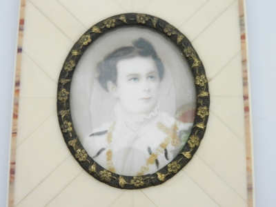 A late 19thC portrait miniature of a military gentleman, depicting a man in dress uniform possibly Ludwig II of Bavaria, signed Silas?, 3.5cm x 4.5cm, in a metal oval frame with applied floral decoration and ivory panelled border, with newspaper article b - 2