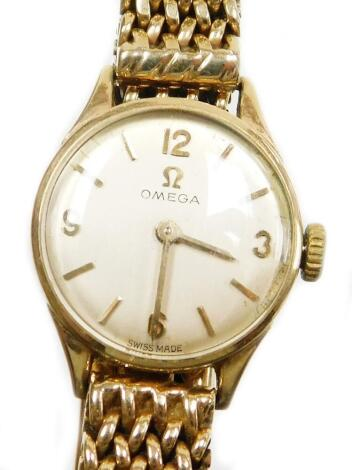 An Omega 9ct gold ladies wristwatch, with small circular silvered dial, 1.2cm diameter, on a four row pleated design thick bracelet, when fully extended 10cm long, 28.6g all in.