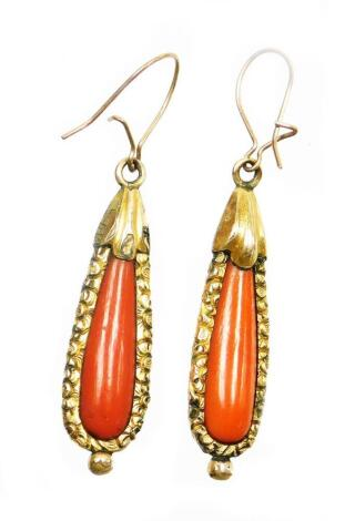 A pair of early to mid 20thC coral drop earrings, each with tear drop shaped coral centre and a gold finished scroll mounts and fan design top, gold plated, the earring 4.5cm long.