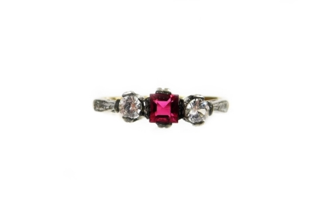 A Victorian three stone dress ring, set with garnet and two imitation diamonds, in a silver setting on a yellow metal band, unmarked, ring size L½, 1.6g all in.