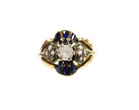 An 18ct gold sapphire and diamond set dress ring, of abstract fan design, with central imitation diamond surrounded by six baguette cut sapphires and eight illusion set tiny diamonds, on splay shoulders stamped Italy, ring size M, 4.2g all in.