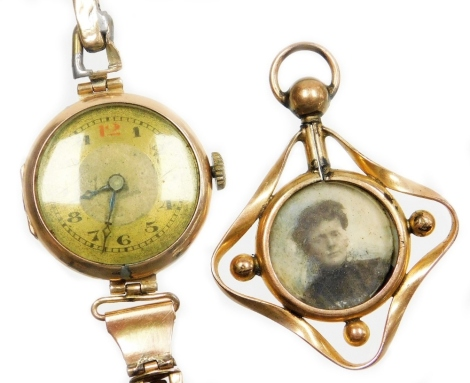 Two items of jewellery, to include a 9ct gold cased wristwatch, with circular silvered colour dial, in a 9ct gold casing, on an expanding 9ct bracelet (AF), 16.6g all in, together with a gilt metal memorial pendant. (2)