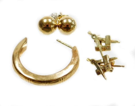 A group of 9ct gold and other earrings, comprising a pair of 9ct gold Masonic earrings (AF), a 9ct gold single hoop earring and a pair of unmarked yellow metal bead studs, 3.5g all in.