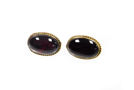 A pair of garnet set stud earrings, each with a rub over rope twist yellow metal border, unmarked lacking backs, 2.3g.
