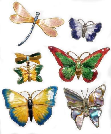 A group of enamelled brooches, to include a small purple butterfly brooch, white metal, stamped sterling silver, 3.5cm wide, a yellow and pale blue butterfly brooch, on a brass back, 5cm wide, a white metal dragonfly brooch, with pink and blue decoration