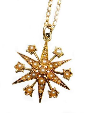 An Edwardian pendant and chain, the star pendant set with various seed pearls, in a yellow metal backing, marked 15ct, 2cm wide, on a fine link yellow metal chain stamped 9ct, 49cm long overall, 7.2g all in.