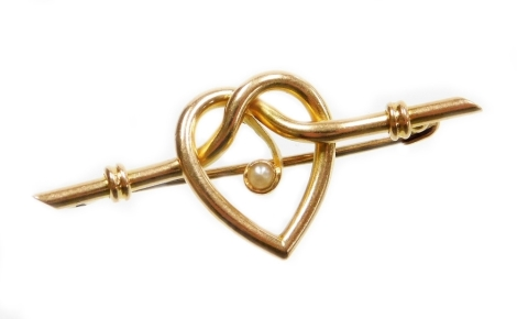 A heart shaped bar brooch, the central heart section with single applied seed pearl, on a ribbed bar brooch stem on pin back, makers stamp to rear in the form of a cross in diamond setting, stamped 15ct, 4.5cm wide, 3g all in.