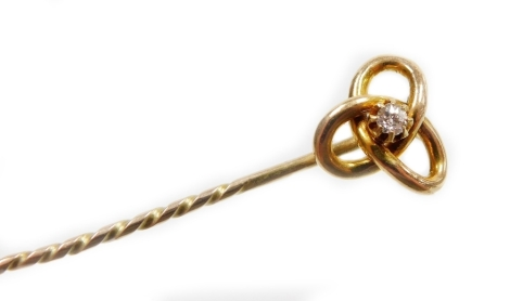 A knot design stick pin, set with single tiny diamond in claw setting with three tier knot on pleated stem, 6cm high, the head 1cm wide, unmarked, 2.5g all in.