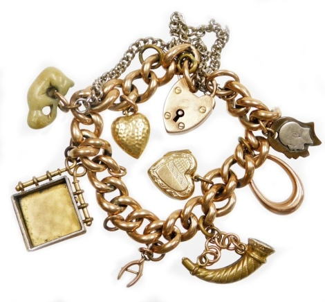 A 9ct gold charm bracelet, with various charms, on curb link bracelet, marked 9c to links, with a 9ct gold heart shaped padlock, charms to include a 9ct gold hoop attachment, a 9ct gold plated heart locket, a brass bugle, a yellow metal horseshoe, a soaps
