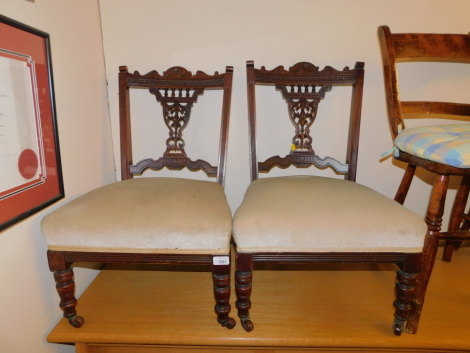 A pair of Victorian nursing chairs, with carved backs and raised on turned legs.