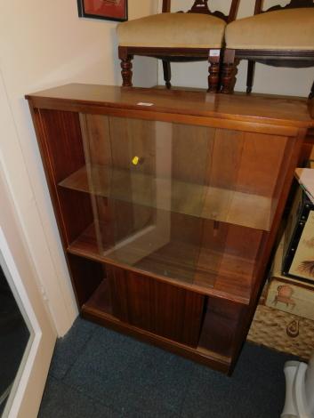 A mid 20thC teak bookcase, with sliding glass doors, above solid sliding doors, 108cm high, 77cm wide, 23cm deep.