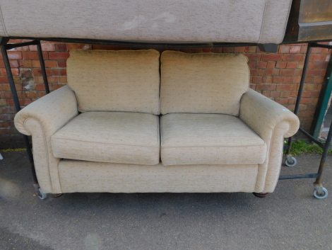 A two seater sofa bed, upholstered in cream patterned chenille fabric, 170cm long.