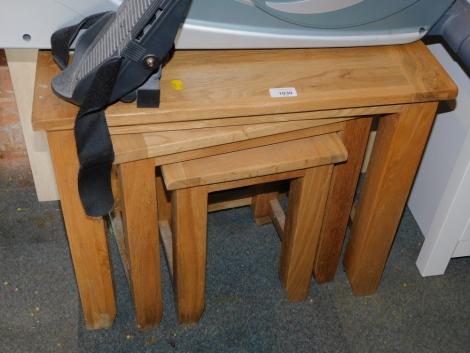A blonde oak nest of tables, largest 52cm high, 61cm wide, 38cm deep.