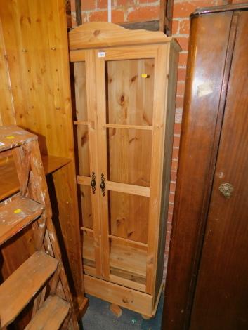 A pine glazed bookcase, enclosing three adjustable shelves, 182cm high, 77cm wide, 31cm deep.