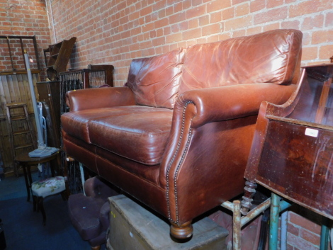 A brown leather two seater sofa, with studded arms, 165cm long.
