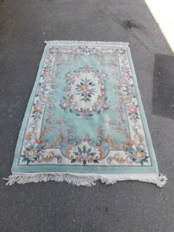 A Chinese wool rug, green ground with floral design, 210cm x 127cm.