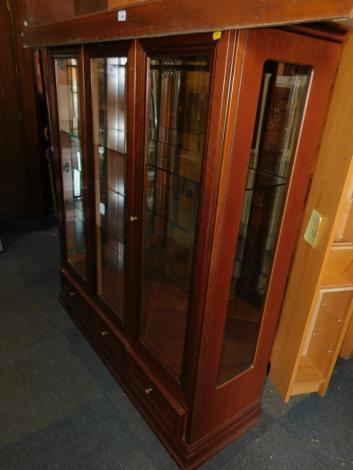 A mahogany effect three door glazed display cabinet, 141cm high, 121cm wide, 38cm deep.