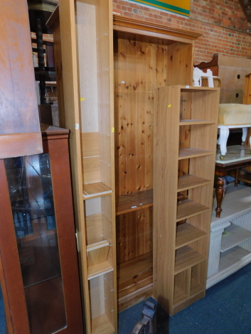 A pine bookcase, enclosing four adjustable shelves, 200cm high, 98cm wide, 32cm deep, together with two CD shelves, 203cm high, 162cm wide. (3)