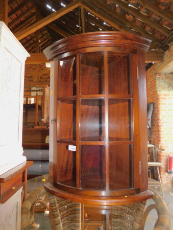 A reproduction mahogany bow front corner cabinet, 67cm high.