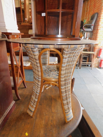 A wicker occasional table, with glass top, 74cm high, 78cm diameter.