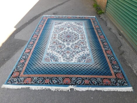 A Bahariye wool rug, blue and cream ground with floral borders and a central medallion, 313cm x 201cm.