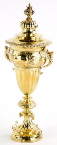 A George V silver gilt two handled trophy cup and cover, engraved J.B.H.M. and E.H.M. August 1878-1928, the lid with a leaf cast finial and a gadrooned border, the base decorated with winged caryatids and leaves etc., the foot decorated with pierced scrol