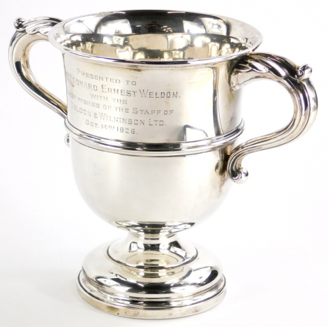 A George V silver two handled trophy cup, engraved 'presented to Mr Leonard Ernest Weldon, with the best wishes of the staff of Weldon and Wilkinson ltd, Oct 14th 1926,' Sheffield 1925 by Walker and Hall, 21½ oz, 20cm high.