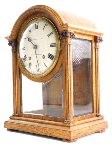 A late 19th/ early 20thC oak mantel clock, the dial stamped H.L. Brown and Sons Ltd London and Sheffield, the arched case with two fluted pillars, on bun feet, 37cm high.