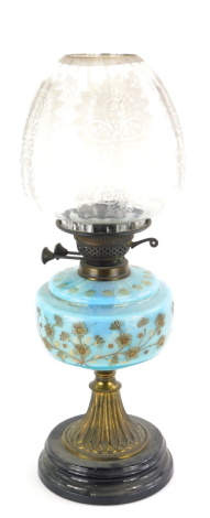 A Victorian oil lamp, with a floral etched shade, a blue glass reservoir decorated with flowers, on a gilt brass support and ceramic base, 59cm high.