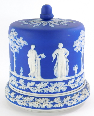 An early 20thC blue Jasperware cheese dome and base, decorated with an acorn finial and Neoclassical figures, probably Wedgwood, unmarked, 26cm high.