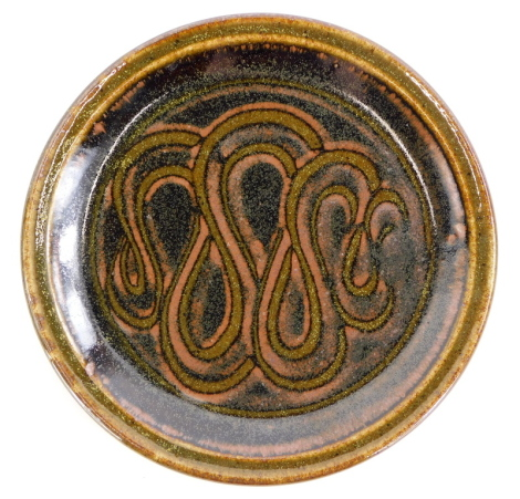 An Edward Hughes (1953-2006) studio pottery plate, decorated with the wipe-pattern, 27cm diameter.