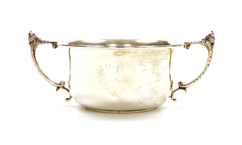 A George V silver trophy cup, the plain circular bowl with angular leafy handles surmounted by acorns on a circular foot, Birmingham 1931, 7cm high, 3.3oz all in.