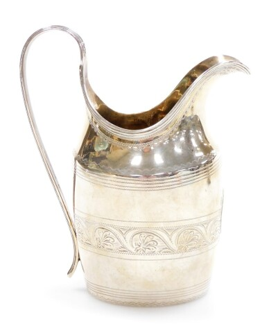 A George III crested silver cream jug, with strapwork handle and oval body engraved with a family crest and bright cut floral banding, London 1806, 13cm high, 4oz.