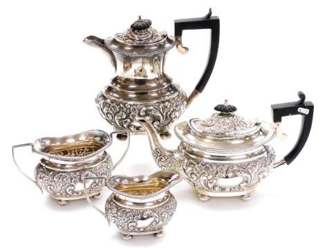 A late Victorian four piece silver bachelors tea and coffee service, comprising coffee pot, 19cm high, teapot, two handled sugar bowl, and milk jug, each with scrolling repoussé decoration and vacant cartouches, on orb feet, Birmingham 1899-1900, 31oz all