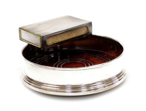 An Elizabeth II silver matchbox case, engine turned with a geometric pattern, Birmingham 1956, 8cm, and an oak lined silver wine coaster, Birmingham 1985, 6oz all in. (2)