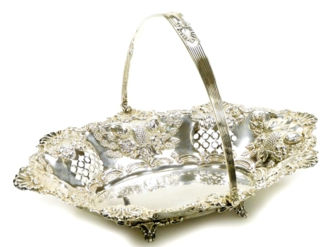 A Victorian silver fruit basket, by Thomas Latham and Earnest Morton, with a shell and scroll outline, heavily repoussé decorated with fruits, with plain oval centre and swing handle, on quadruple scroll feet, Birmingham 1899, 29cm long, 13oz.