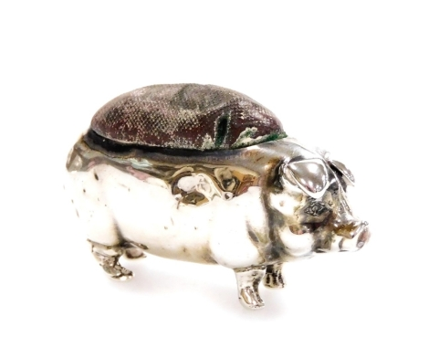 A George V novelty silver pig pin cushion, with velvet top in standing pose, Birmingham probably 1910 date letter rubbed, 5cm long, 0.3oz all in.