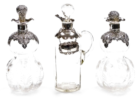 A pair of cut glass and silver topped liqueur decanters, each with embossed stopper and flared rims, Birmingham 1924, 25cm high, and a silver topped glass claret jug, with silver collar, London 1922, with a later silver Whisky label. (3)
