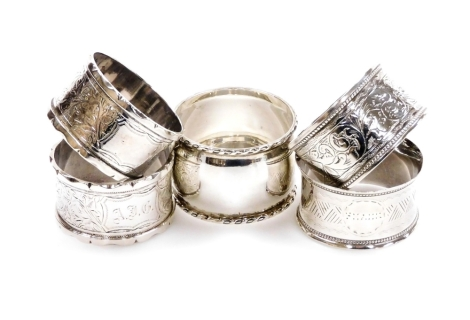 Five various silver napkin rings, to include a Victorian napkin ring of shaped circular form, heavily decorated with scrolls, initial cartouche, Birmingham 1887, and four others, 4oz all in. (5)