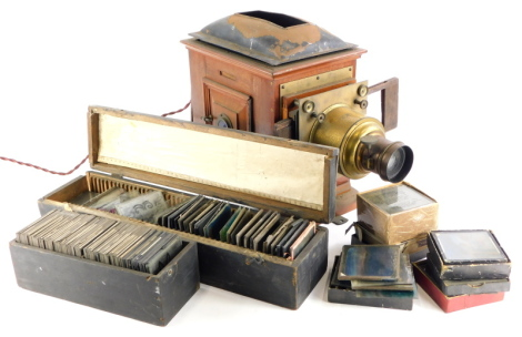 A late Victorian mahogany and brass magic lantern, with a quantity of magic lantern slides, various types to include topographical, religion, etc.